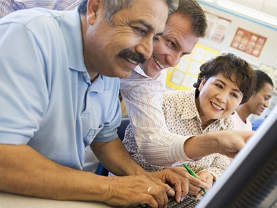 Mature students learning computer skills in classroom