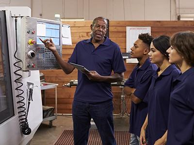 Older Engineer Training Apprentices OEngineer Training Apprentices On CNC Machinen CNC Machine