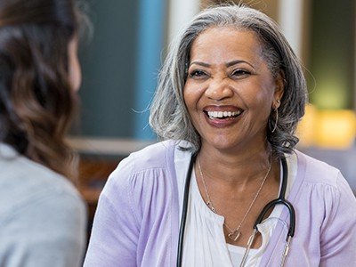 Older medical professional talks with patient